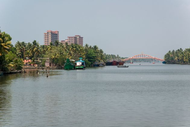 Mata Amritanandamayi's high-rise building ashram beside a water canal and between palm trees in the middle...
