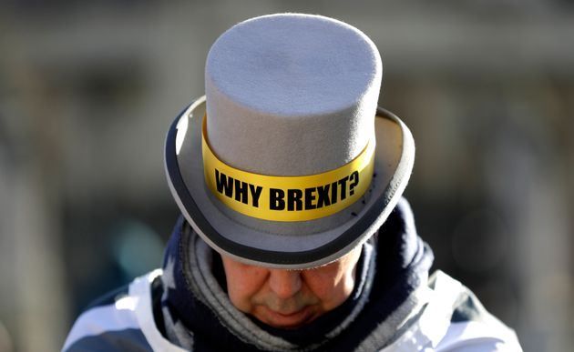 Why Brexit? written on the hat of anti-Brexit campaigner Steve Bray as he stands outside parliament in