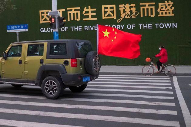 Un véhicule portant le drapeau chinois passe à côté d'une femme portant un...