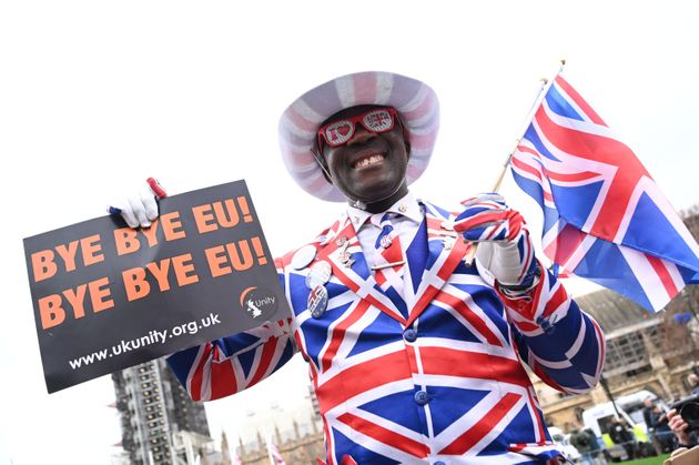 Brexit supporter Joseph Afrane is decked out in the colours of the British flag Friday as he holds a sign saying