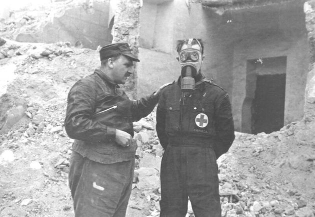 Haldane with a volunteer, demonstrating a gas mask in Spain, c. 1936-37, Source: Imperial War