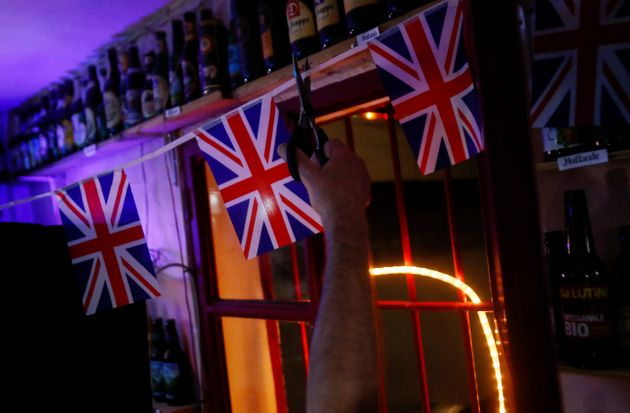 British resident Paul Darwent cuts a cord with British flags inside his bar after the countdown which...