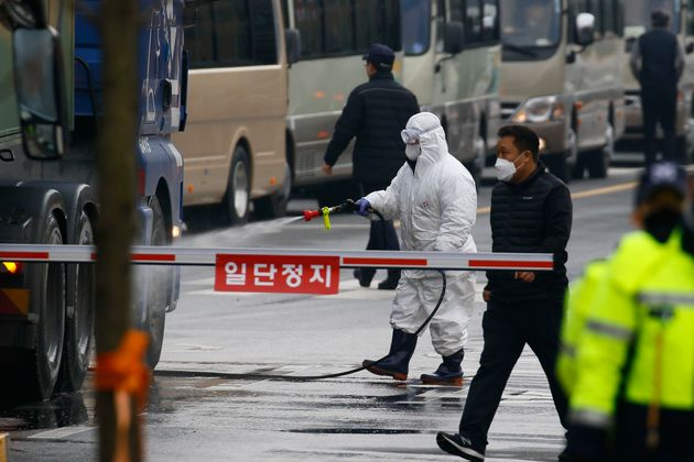 An official disinfects a road near a state facility in Jincheon, some 90 kilometers southeast of Seoul,...