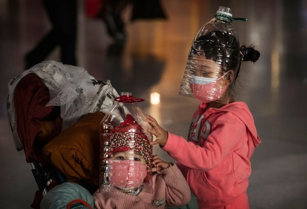 BEIJING, CHINA - JANUARY 30: Chinese children wear plastic bottles as makeshift homemade protection and...