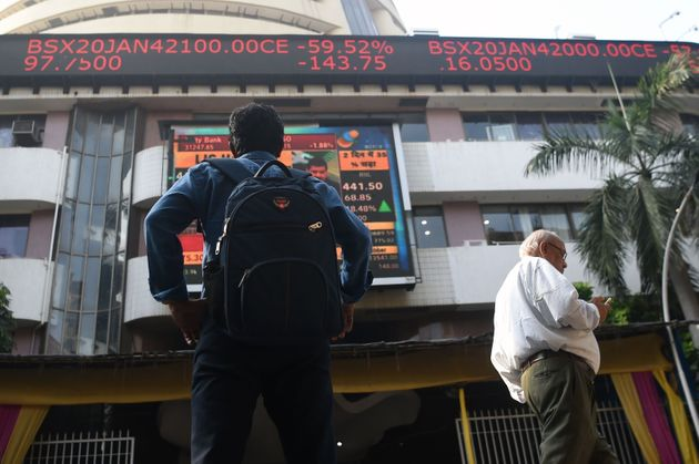 A man watches share prices on a digital broadcast outside the Bombay Stock Exchange (BSE) in Mumbai on...