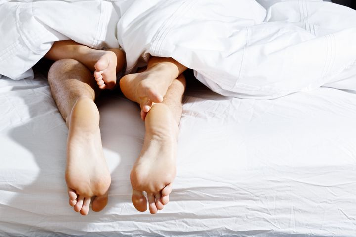 The entwined feet of an anonymous couple having sex under a white duvet.