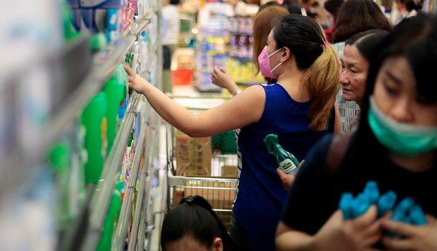 Des habitants font des réserves de bouteilles d'alcool le 30 janvier dans la banlieue de Manille,...
