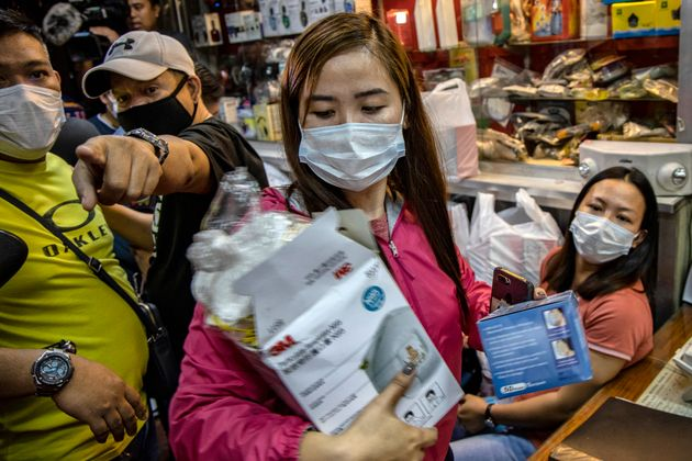 Police officers in plainclothes seize face masks from a medical supply shop that was raided for allegedly...