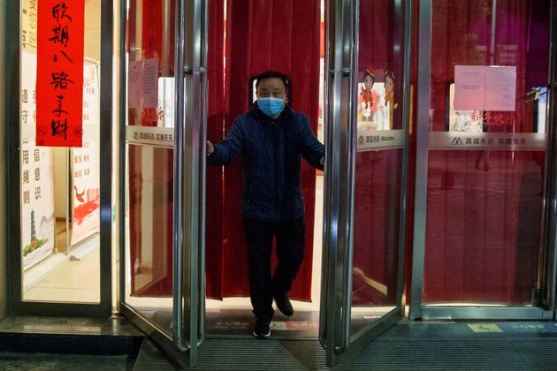 A man wearing a face mask closes a supermarket in Jiujiang, Jiangxi province, China, as the country is hit by an outbreak of a new coronavirus, February 1, 2020.  REUTERS/Thomas Peter