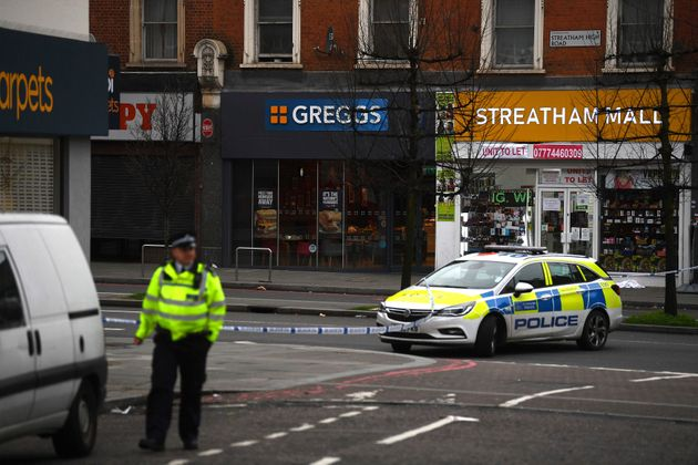 Police attend the scene after an incident in London on Sunday. Police say officers shot a man during...