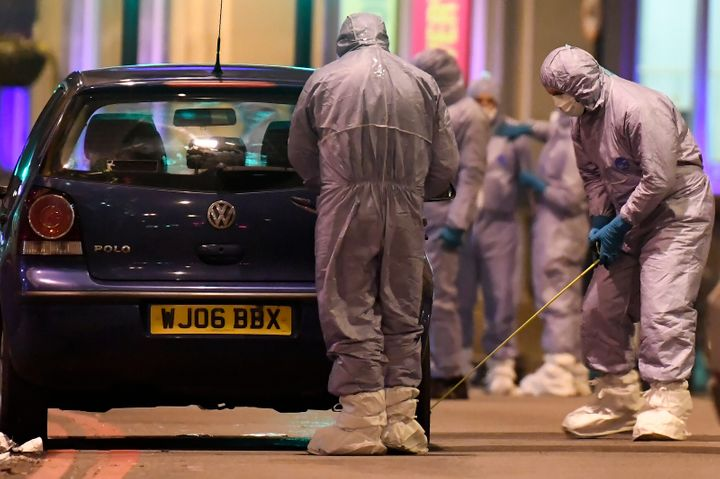 Police forensic officers work near a car at the scene after a stabbing incident in Streatham, London, on Sunday.