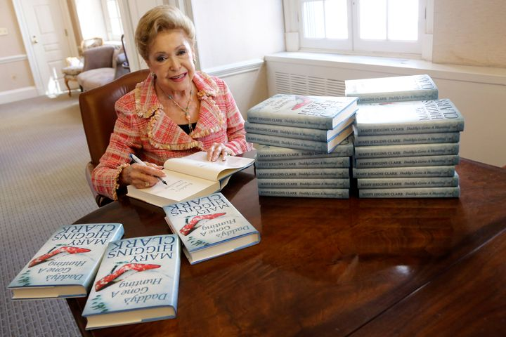 """Clark signs copies of her book """"Daddy's Gone A Hunting"""" at the Simon & Schuster office in New York in 2013."""