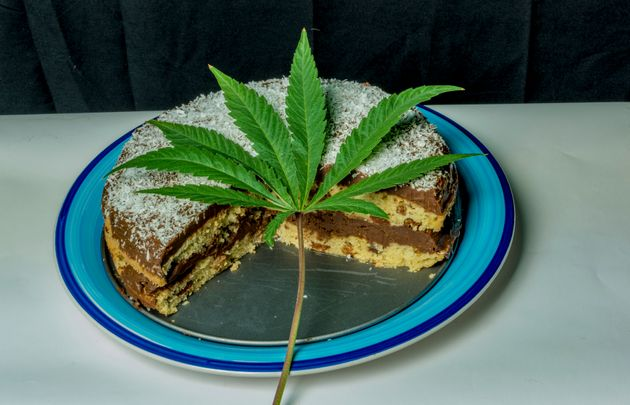 A stock image of a cake with a cannabis leaf on