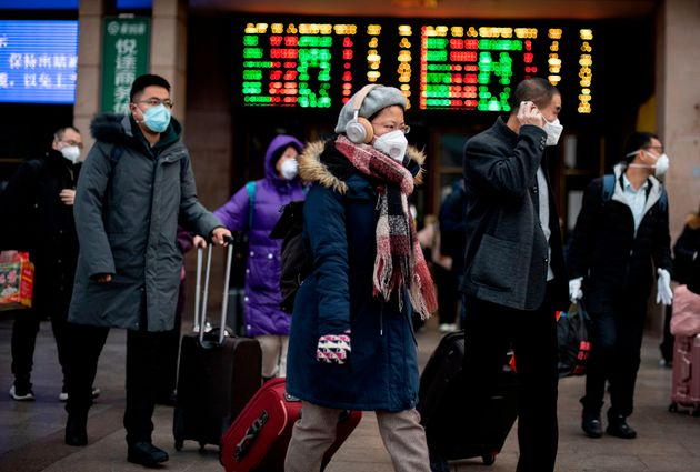 Passengers wearing facemasks arrive from different provinces at the Beijing Railway Station on February...