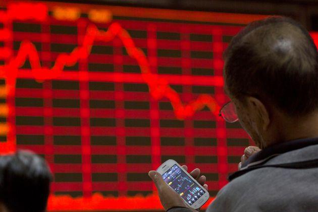 このストックフォトでは、投資家が北京の証券会社で株価を表示しているスマートフォンを見て...