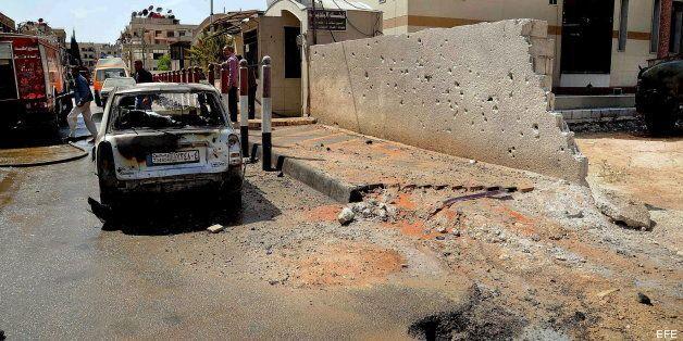 Un coche al lado de un edificio municipal alcanzado por disparos de