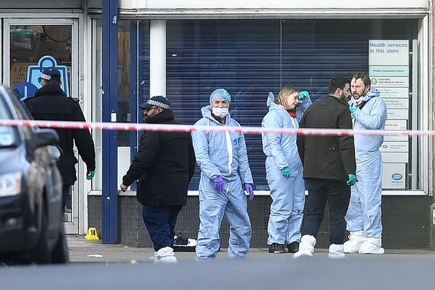 Police forensic officers work outside of a Boots store on Streatham High Road in south London on February...