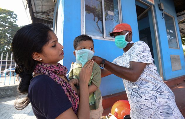 A man wearing a surgical mask makes a child wear one outside the government general hospital where a...