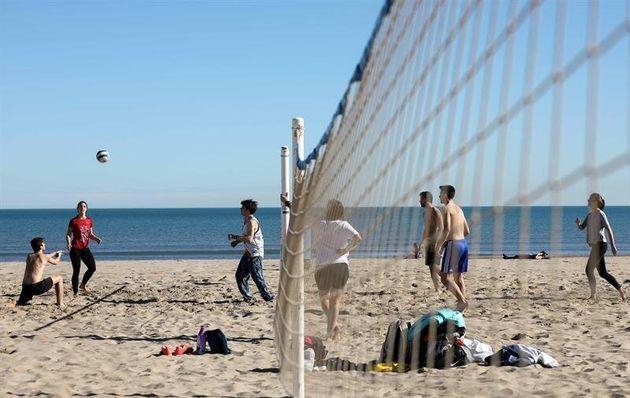 Varias personas disfrutan de un día de calor en la playa de la Malvarrosa de