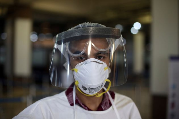An Afghan health worker wearing protective gear waits to check passengers during screening of travelers...