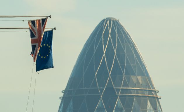 A Union Flag and a European Union flag seen alongside 30 St Mary Axe, also known as the Gherkin, in the...