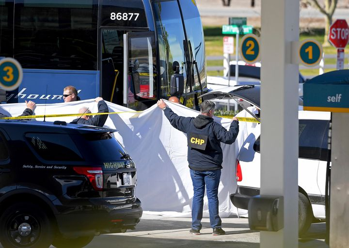Coroner's officials work behind a drape to remove the body of a person who was killed when a gunman opened fire aboard a pack