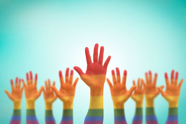 LGBT equal rights movement and gender equality concept with rainbow flag on people's hands