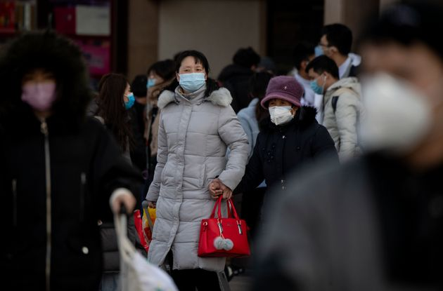 Travellers wearing facemasks arrive from various provinces at the Beijing Railway Station on February...