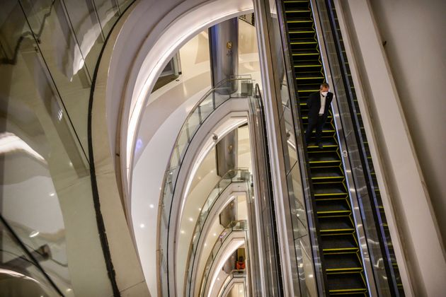 A Chinese man wears a protective mask as he rides an escalator in an empty shopping mall in the Central...