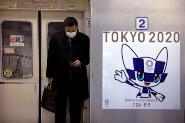 A poster promoting the Tokyo 2020 Olympics is posted next a train door as a commuter wearing a mask looks...