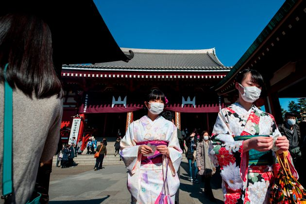 Women in traditional Japanese kimonos wear face masks to help prevent the spread of the SARS-like virus...
