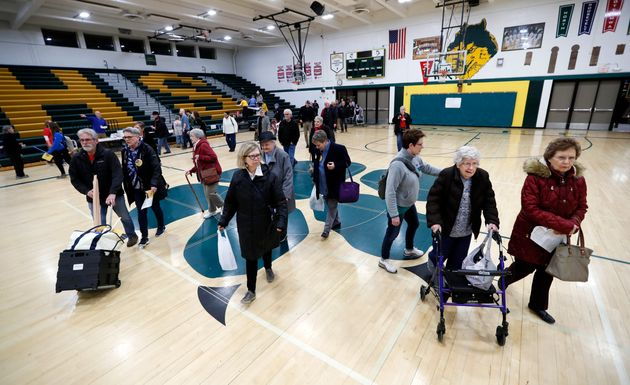 Des Moines, Iowa, residents enter a caucus site at Hoover High School on