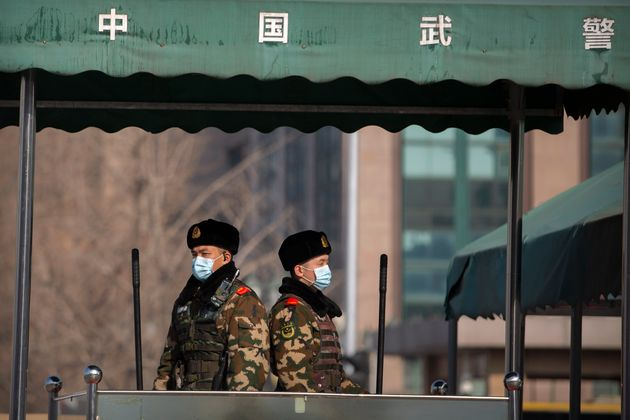 Chinese paramilitary police wear face masks as they stand guard outside the Beijing Railway Station in...