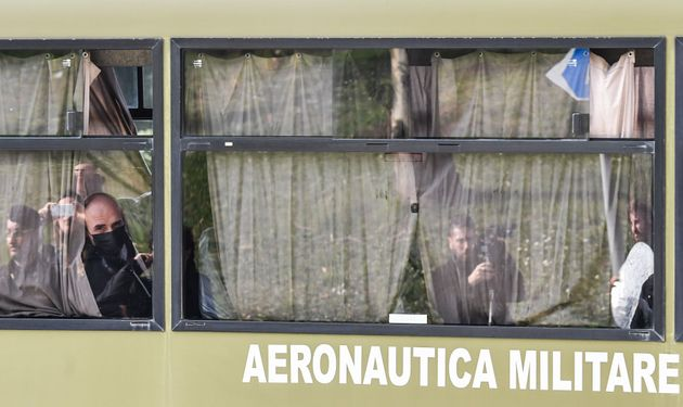 A passenger wearing a protective mask (L) looks out from a military coach transporting Italian citizens...
