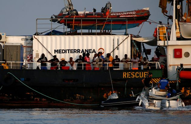 Rescued migrants line the deck of the Mare Jonio, operated by Italian charity Mediterranea Saving Humans,...