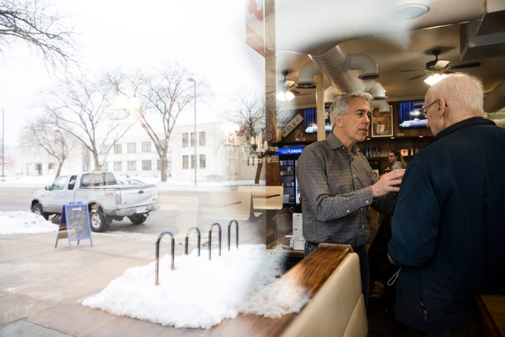 Republican presidential candidate Joe Walsh (center) is seen through a window during a campaign event at Riley's Cafe on Jan.