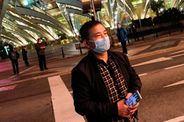 A man wearing mask walks in front of Casino Lisboa, before its temporary closing, following the coronavirus outbreak in Macau, China February 4, 2020. REUTERS/Tyrone Siu