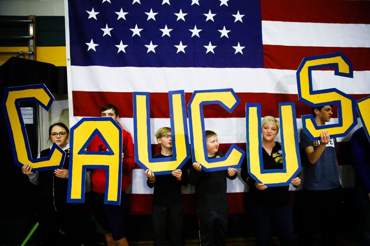 """Attendees hold letters that read """"CAUCUS"""" during a campaign event for Democratic presidential candidate Pete Buttigieg on Feb"""