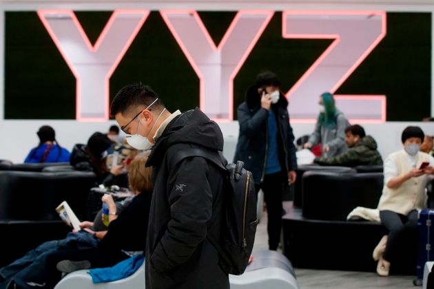 Travellers are seen wearing masks at the international arrivals area at the Toronto Pearson Airport in...