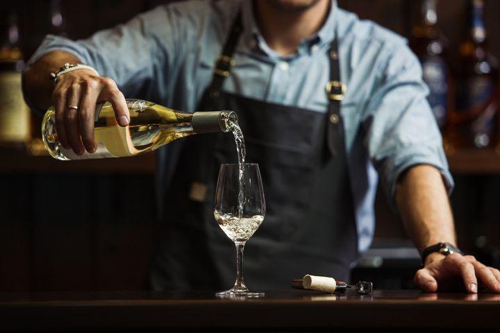 Ενας sommelier σερβίρει λευκό κρασί.