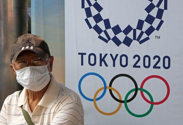 Un hombre con mascarilla junto al cartel de los Juegos Olímpicos