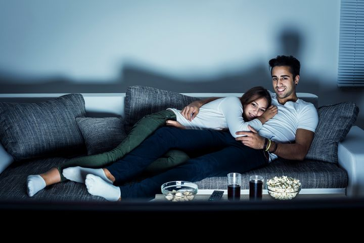 Young couple watching a movie at home, lying on sofa. Both Caucasian, casual, about 25 years old.