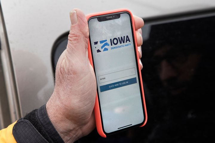 Precinct captain Carl Voss of Des Moines displays the Iowa Democratic Party caucus reporting app on his phone outside of the