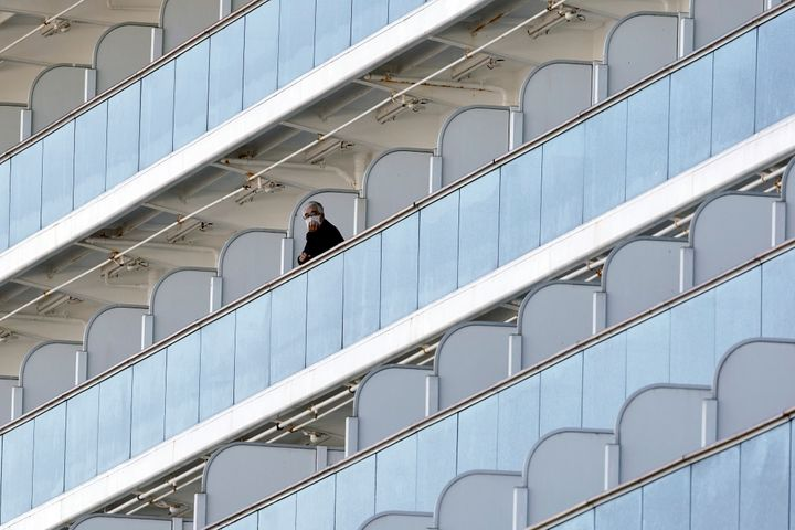 A passenger stands outside on the balcony of the cruise ship Diamond Princess anchored at the Yokohama Port on Feb. 6, 2020,