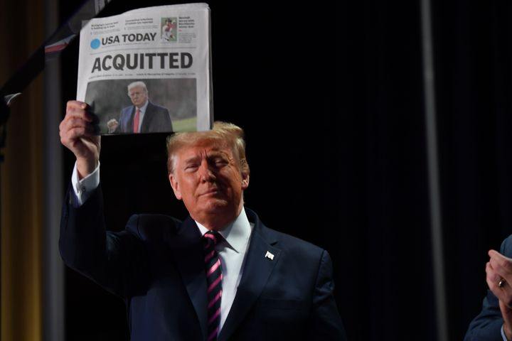 """US President Donald Trump holds up a newspaper that displays a headline """"Acquitted"""" as he arrives to speak at the 68th annual"""