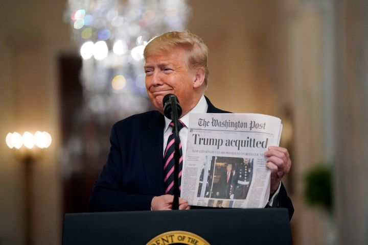 President Donald Trump holds a copy of The Washington Post as he speaks in the East Room of the White House on Thursday.