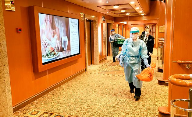 Medical workers in protective gear walk on the cruise ship Diamond Princess in this Feb. 4 photo taken...