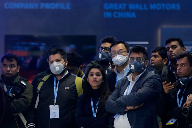 Delegates wear face mask as they attend an event at the Auto Expo in Greater Noida, near New Delhi,