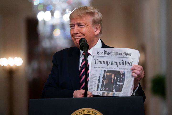 President Donald Trump holds up a newspaper trumpeting his acquittal as he spoke in the East Room of the White House on Thurs