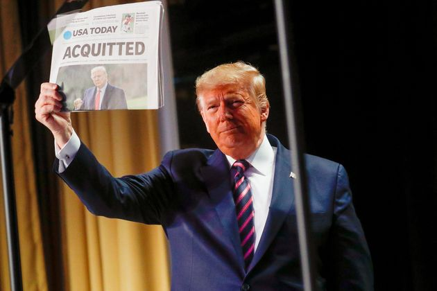 President Donald Trump holds up a copy of USA Today showing news of his acquittal in the Senate impeachment...